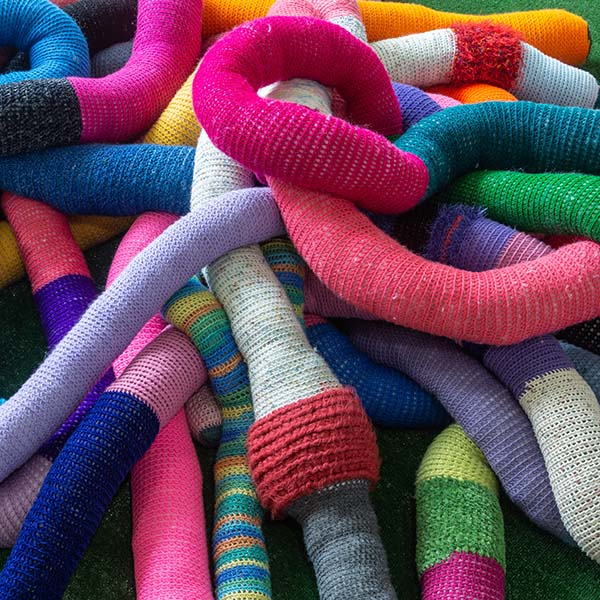thumbnail link showing an photograph of crocheted colorful worm sculptures