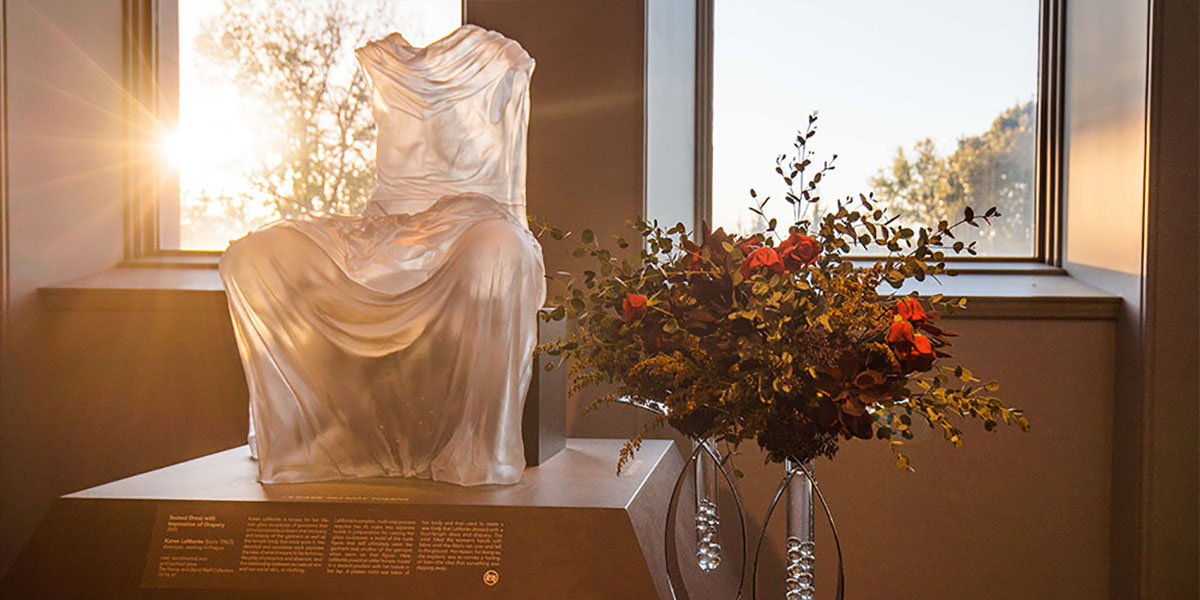 Statue in a museum next to a bouquet of flowers.