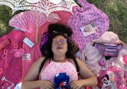Picture of a person lying on a pink blanket and a variety of pink items.